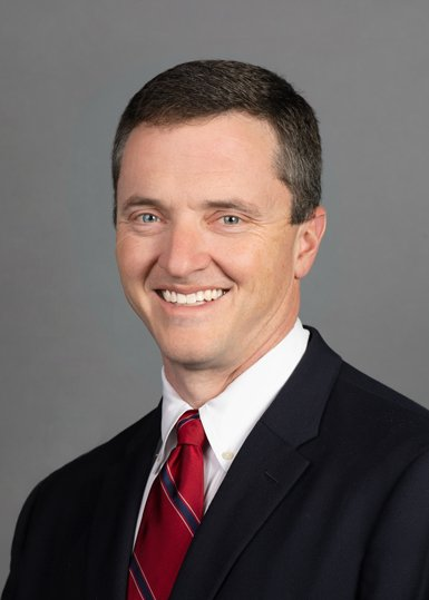 Orthopedic surgeon smiling and wearing a suit with a red tie.
